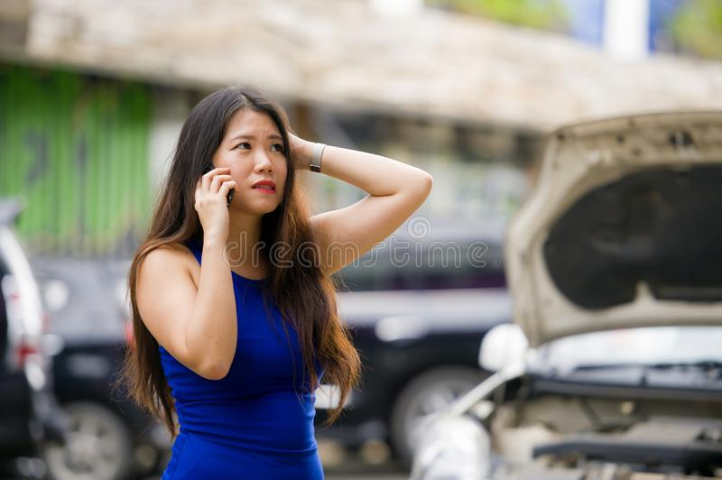 Asian Korean woman in stress stranded on street suffering car engine failure having mechanic problem calling on mobile phone for royalty free stock images