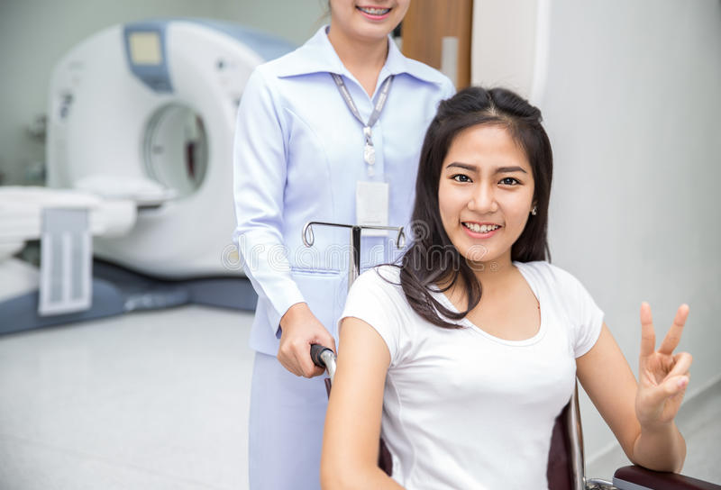 Asian lady sit on wheelshair. After exam her body by a CT Scan with nurse stock photos