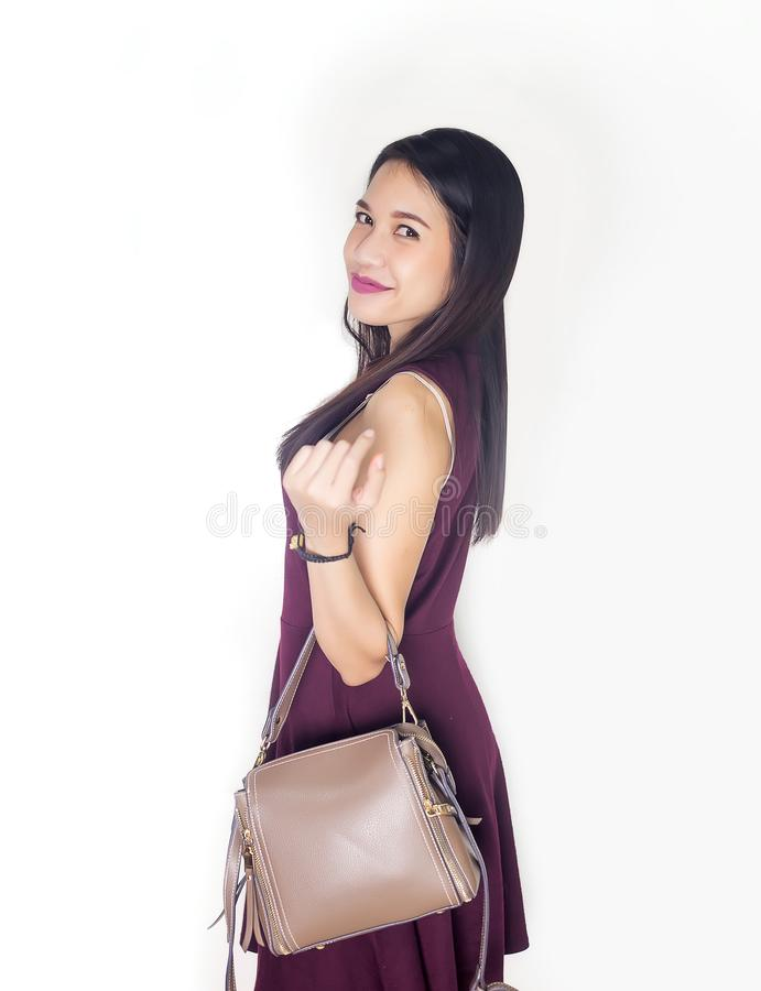 Asian lady smile withholding leather bag on studio. Asian lady portrait on white background stock photography
