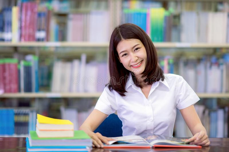 Asian lady student smile and do homework in libraly royalty free stock image