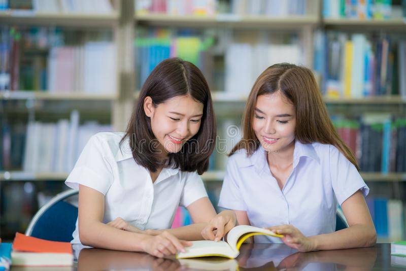 Asian lady student study and do home work in library in University. Education and university concept stock photos