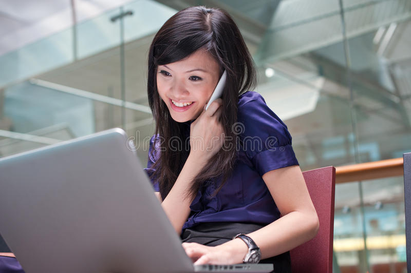 Asian lady working on her laptop stock photography