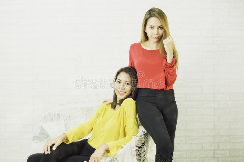 Asian lesbian women LGBT lesbians wearing yellow and red shirts, long hair, post poses, taking pictures happily with the concept stock image