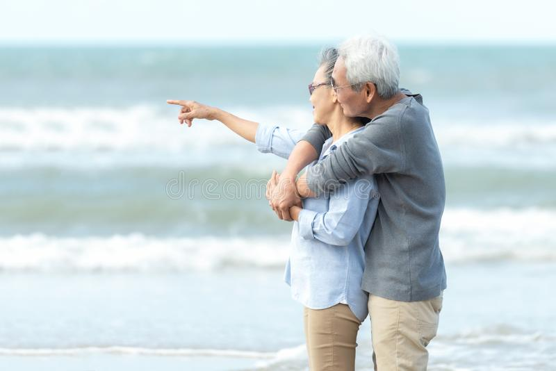 Asian Lifestyle senior couple pointing and hug, stand see beach happy in love romantic and relax time. Tourism elderly family tr royalty free stock photography