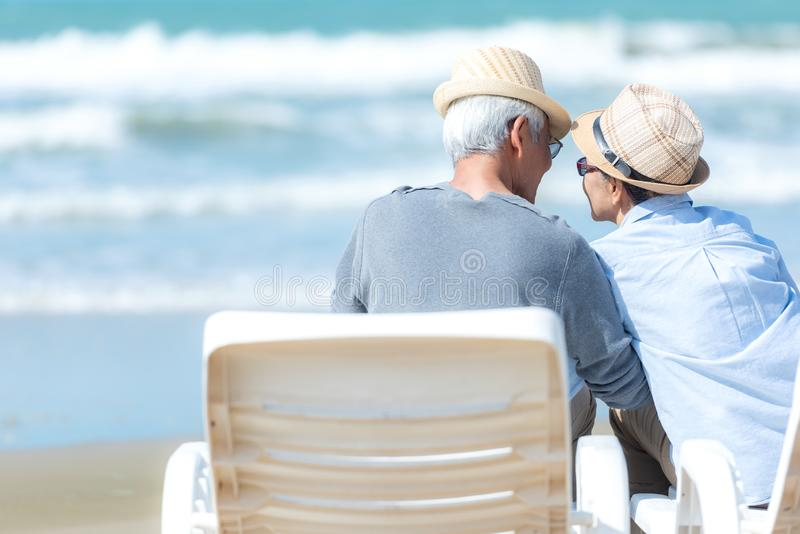Asian Lifestyle senior couple sitting on the chair beach.  People old happy in love romantic and relax time on the sand beach. royalty free stock photos