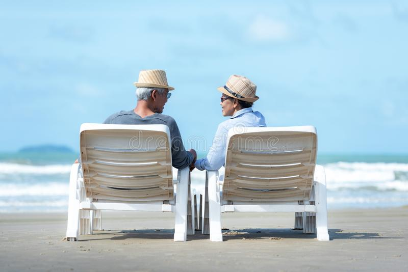 Asian Lifestyle senior couple sitting on the chair beach.  People old happy in love romantic and relax time on the sand beach. royalty free stock images