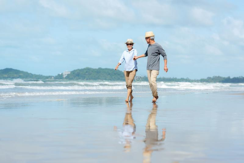 Asian Lifestyle senior elderly couple running on the beach happy enjoy in love romantic and relax time. stock photography