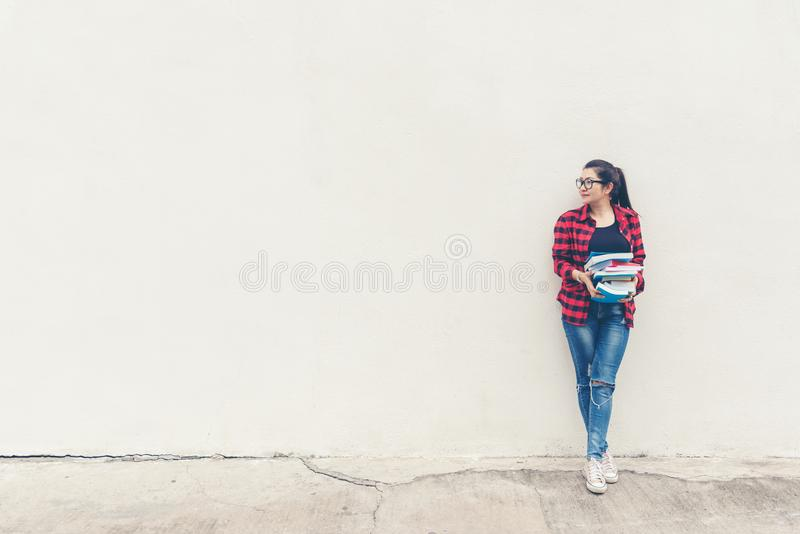 Asian lifestyle woman standing and holding book for education outdoors,  free space over white brick wall. royalty free stock image