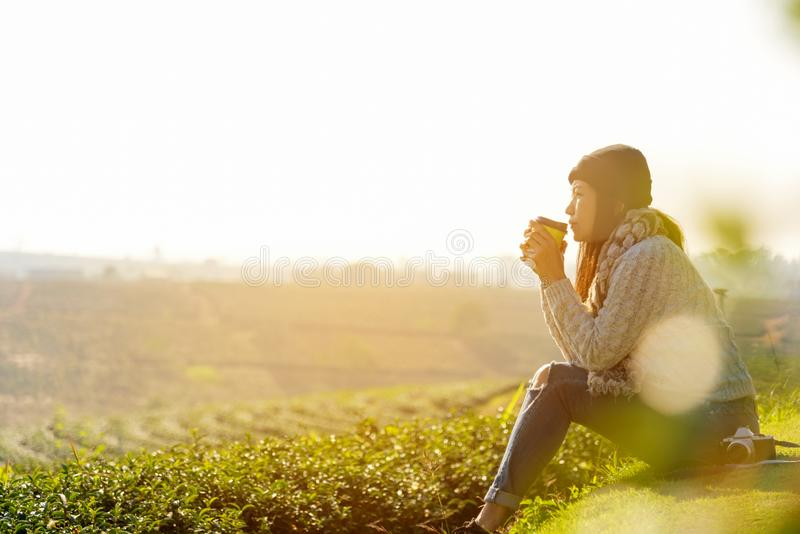 Asian lifestyle women wearing sweater, sitting and drinking hot coffee or tea relax outdoor in the sunrise morning sunny day at te stock image