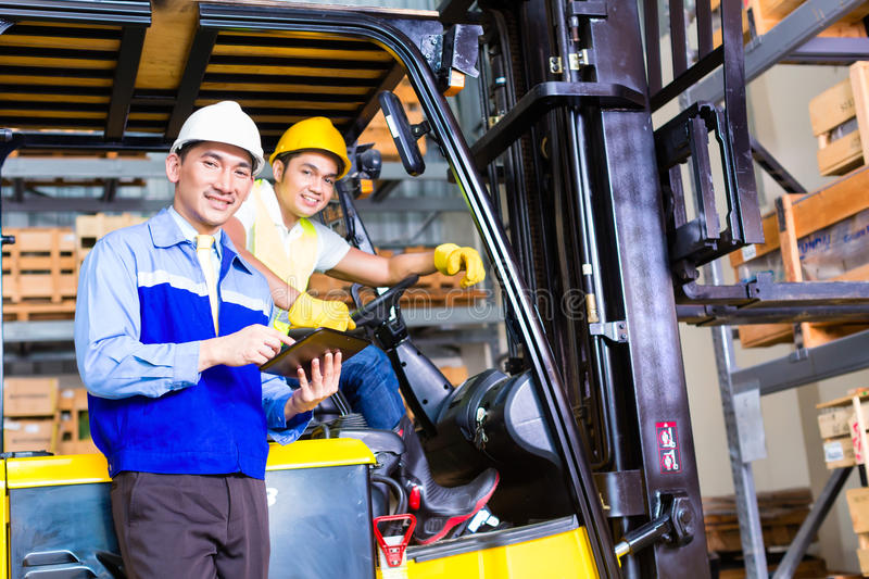 Asian lift truck driver and foreman in storage. Asian fork lift truck driver discussing checklist with foreman in warehouse royalty free stock photo