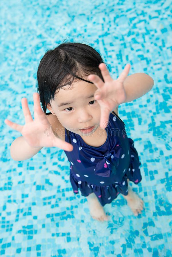 Asian little baby girl in swimming pool. Portrait of Asian little baby girl playing in swimming pool royalty free stock photography