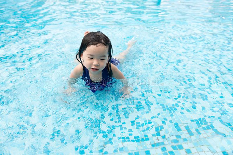 Asian little baby girl in swimming pool. Portrait of Asian little baby girl playing in swimming pool stock image