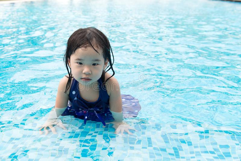 Asian little baby girl in swimming pool. Portrait of Asian little baby girl playing in swimming pool royalty free stock photo