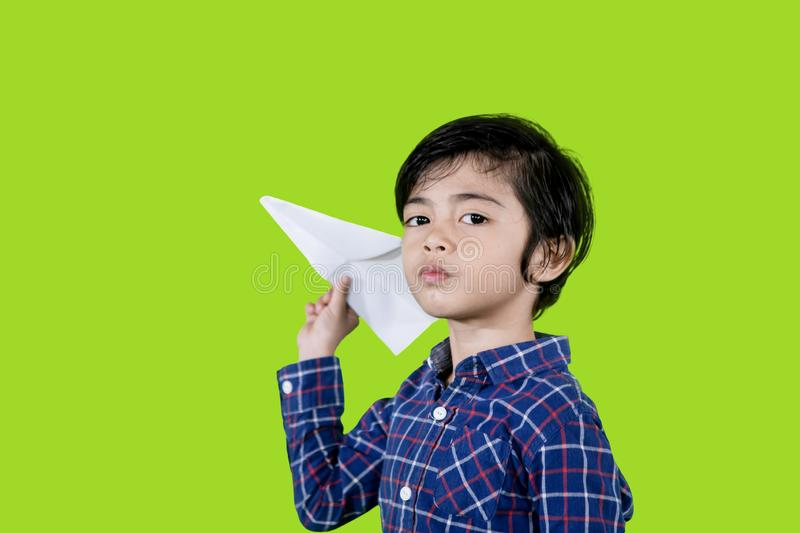 Asian little boy playing a paper plane on studio. Picture of Asian little boy playing a paper plane while playing in the studio with green screen background stock images