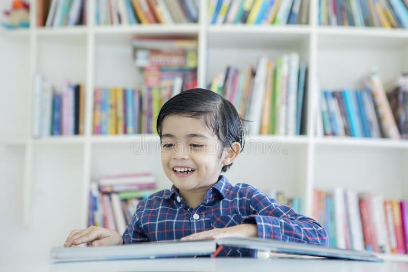Asian little boy reading a book in the library royalty free stock photo