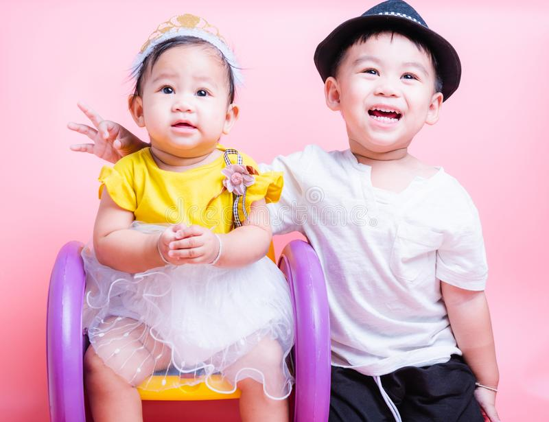 Asian Little brother boy and her baby girl in beautiful dress sitting on chair,  Family with children royalty free stock photography