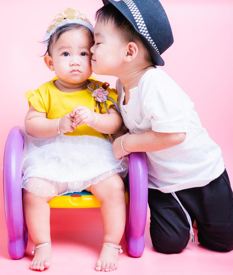 Asian Little brother and her baby girl in beautiful dress sitting on chair,  Family with children in studio royalty free stock images