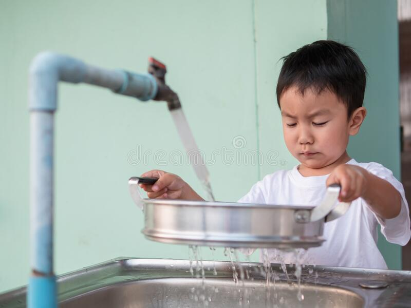 Asian little child boy helping to wash pot with happy face in relaxing family time. royalty free stock photography