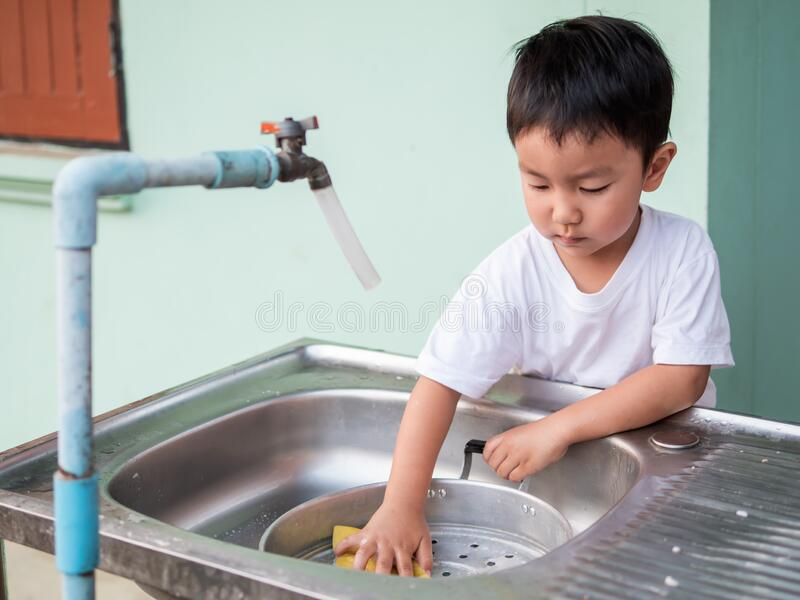 Asian little child boy helping to wash pot with happy face in relaxing family time. royalty free stock image