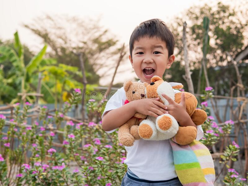 Asian little child boy holding, hugging favorite teddy bear with smiling cheerful happy face. stock images