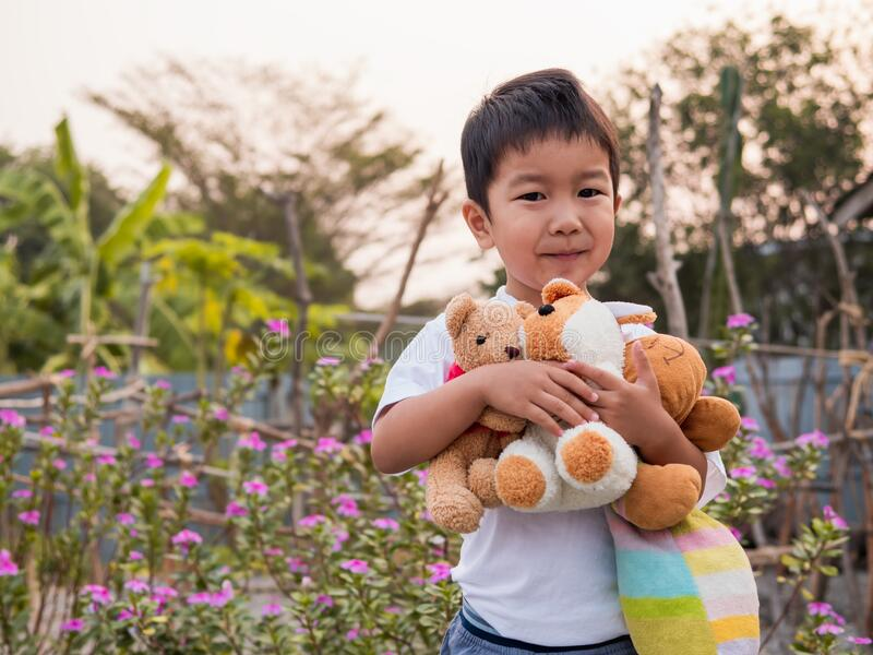 Asian little child boy holding, hugging favorite teddy bear with smiling happy face. royalty free stock photo