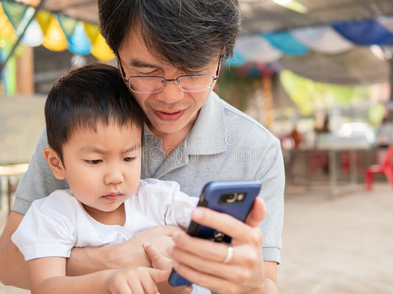 Asian little child boy watching smart phone with dad with happy face. royalty free stock photo