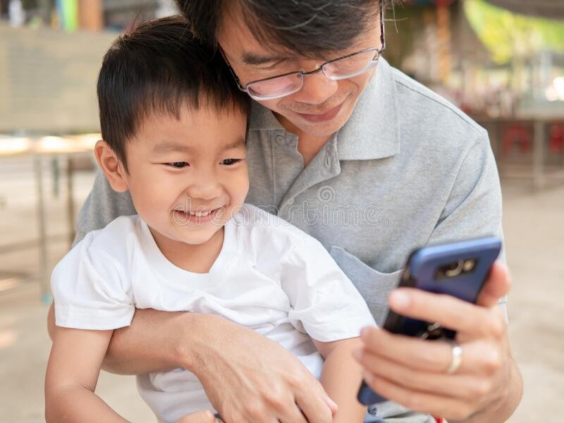 Asian little child boy watching smart phone with dad with happy smiling face. stock images