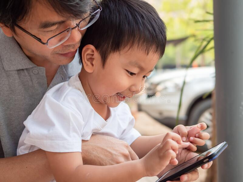 Asian little child boy watching smart phone with dad with happy smiling face. royalty free stock photo