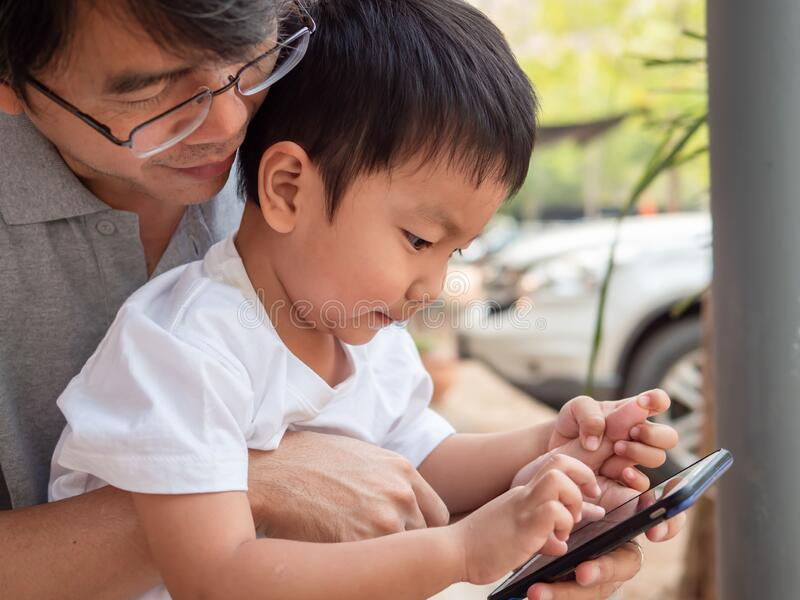 Asian little child boy watching smart phone with dad with happy smiling face. stock photography