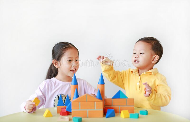 Asian little child girl and baby boy playing a colorful wood block toy on table over white background. Sister and her brother royalty free stock image