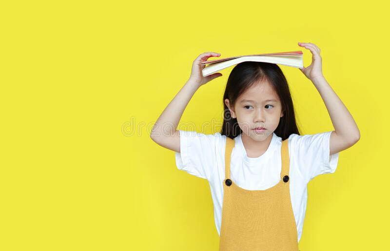 Asian little child girl with book on head and looking beside with copy space isolated on yellow background. Portrait of schoolgirl royalty free stock photography