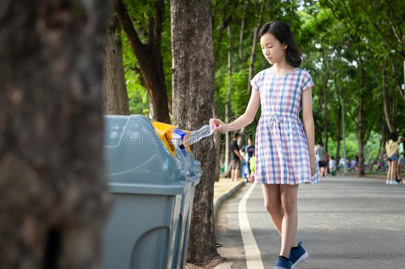 Asian little child girl hand holding plastic bottle,putting plastic water bottle in recycling bin,tourist woman hand throwing. Garbage in a trash bin on street royalty free stock photo
