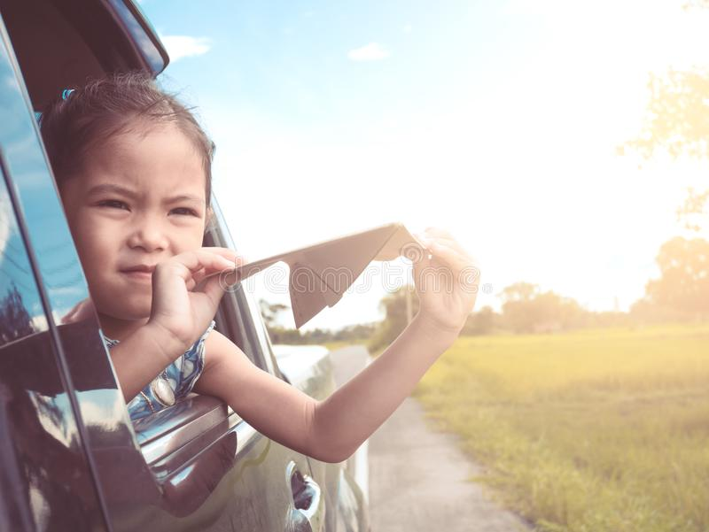 Asian little child girl having fun to play with paper airplane. Cute asian little child girl having fun to play with toy paper airplane out of car window in the royalty free stock photography
