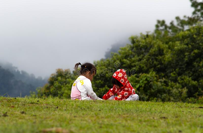 Asian little child girl helped to put shoes on the sister on the grass at Ang Khang mountain, Fang Chiang Mai. Tourist attraction. In northern of Thailand royalty free stock images