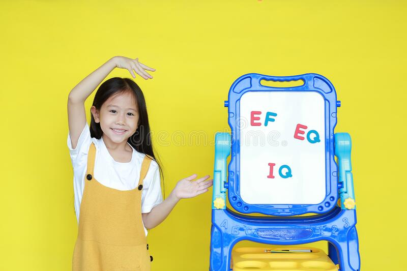 Asian little child girl present something on white board for study in class. Schoolgirl present text EF, EQ and IQ on whiteboard royalty free stock photo