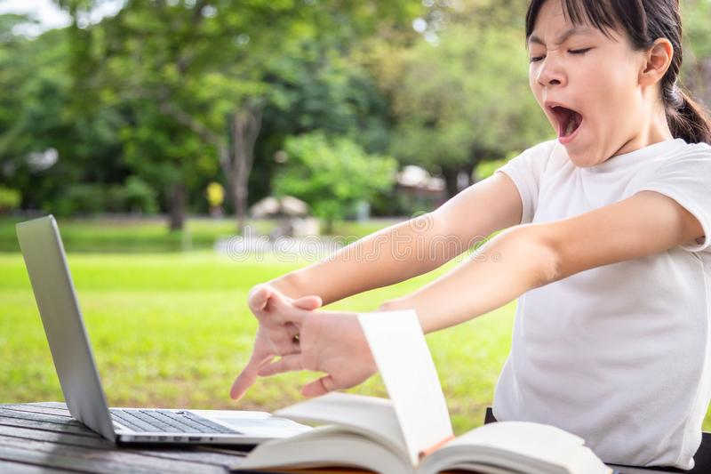 Asian little child girl stretching and bored while reading book,female student with laptop computer on table,she is yawns,tired stock photo