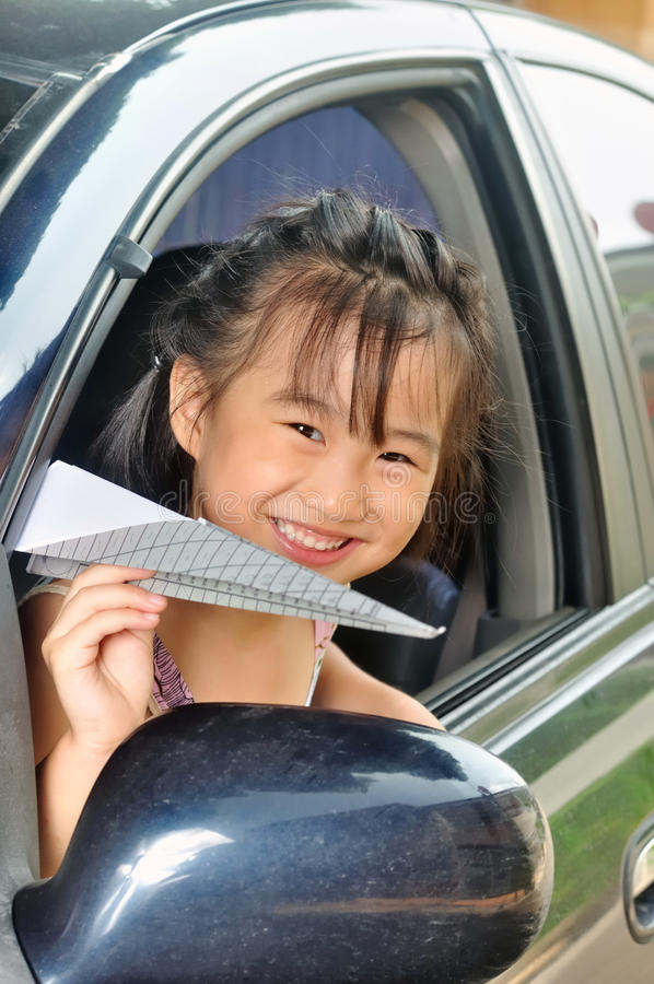 Asian little child holding paper plane in the car stock photo