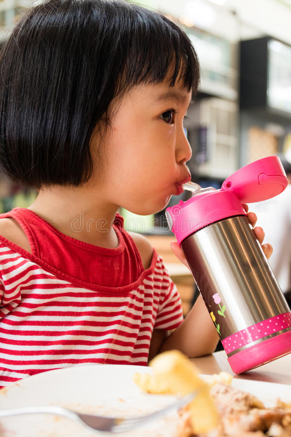 Asian Little Chinese Girl Drinking Water from Stainless Steel Bo stock photos