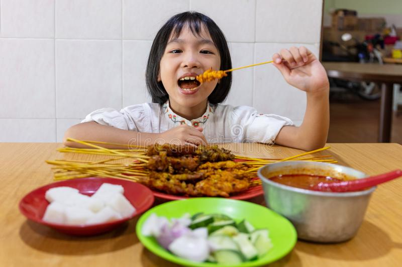 Asian Little Chinese Girl eating satay royalty free stock photography