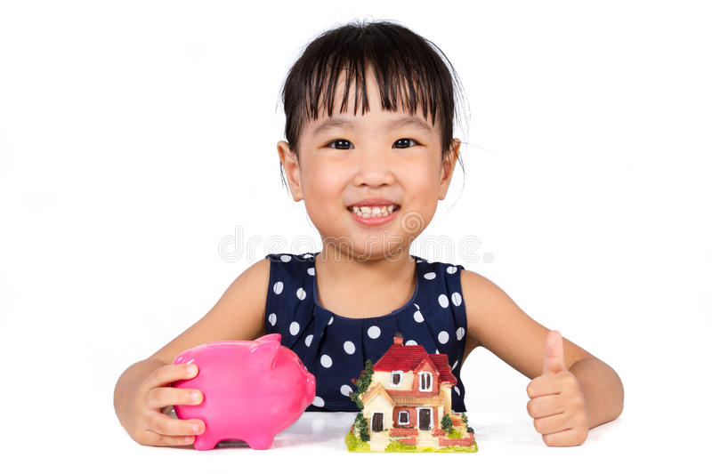 Asian Little Chinese Girl Saving Money for Property Concept. Isolated on White Background royalty free stock image