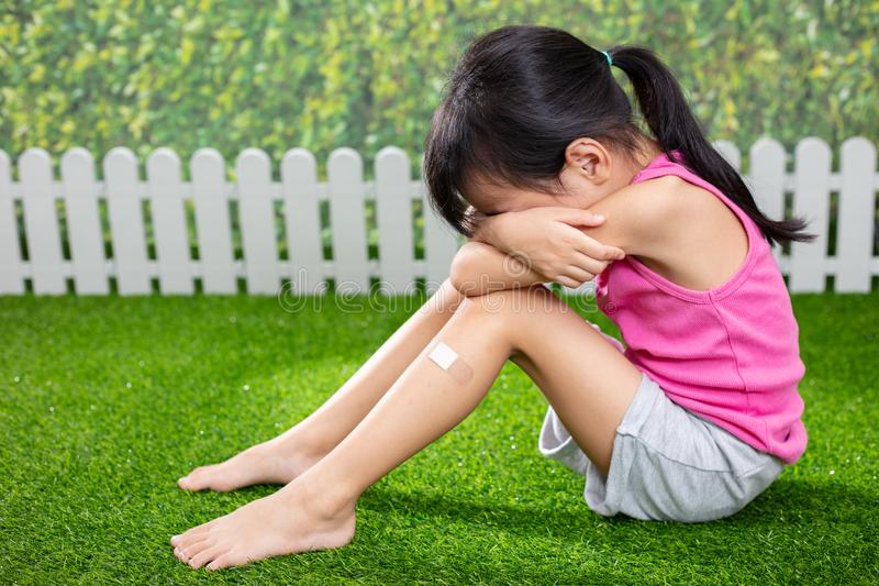 Asian Little Chinese girl sitting on the grass and crying royalty free stock photo