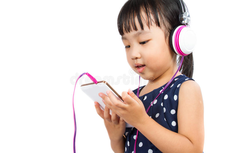 Asian Little Chinese Girl Using Mobile Phone with Headset stock image
