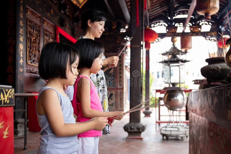 Asian Little Chinese Sisters and mother praying with burning incense sticks stock image