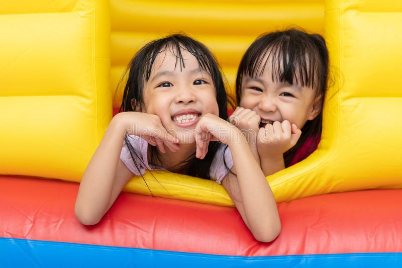 Asian Little Chinese sisters playing at inflatable castle stock photos