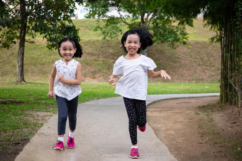 Asian Little Chinese Sisters running happily stock photo