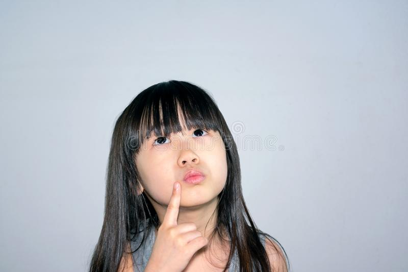 Child Recalling Memory. Asian Little Girl Actively thinks and Jogs Memory and Brainstorms New Ideas stock image