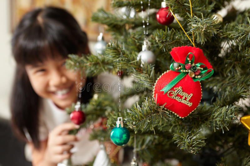 Asian little girl and Christmas tree. Smiling Asian little girl and Christmas tree at home royalty free stock images