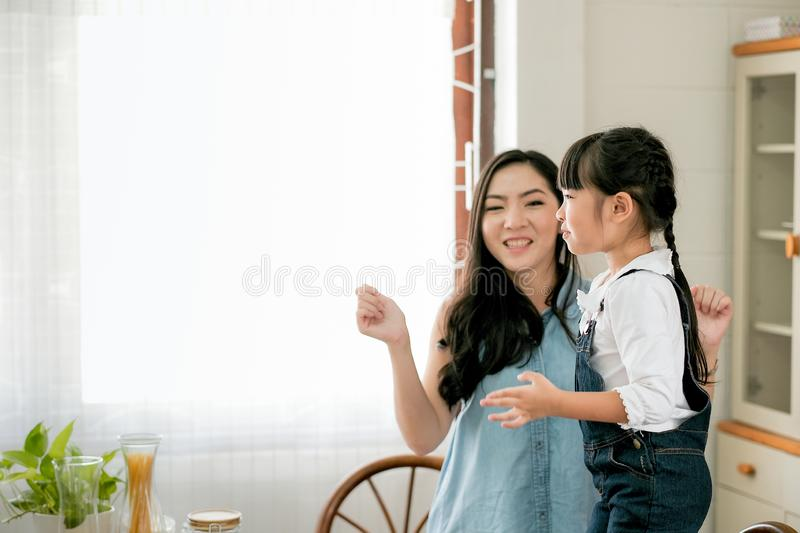 Asian little girl dance with her mother in the kitchen in the morning and she look to the window with happy emotion stock photography