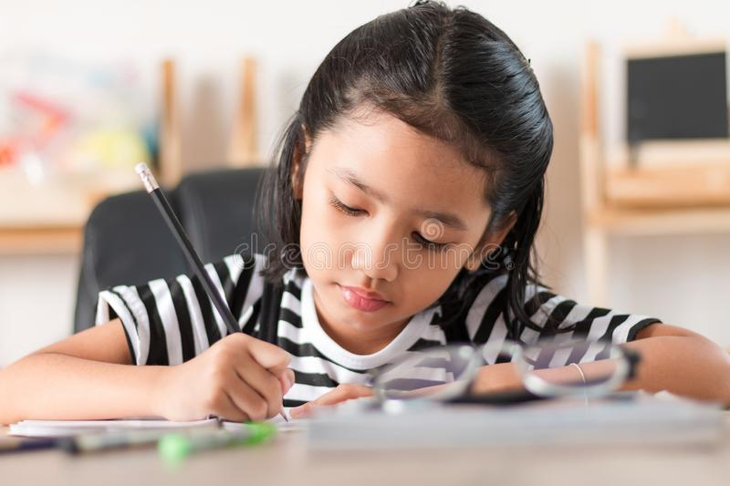 Asian little girl doing homework and pointing finger on wooden table select focus shallow depth of field royalty free stock photo