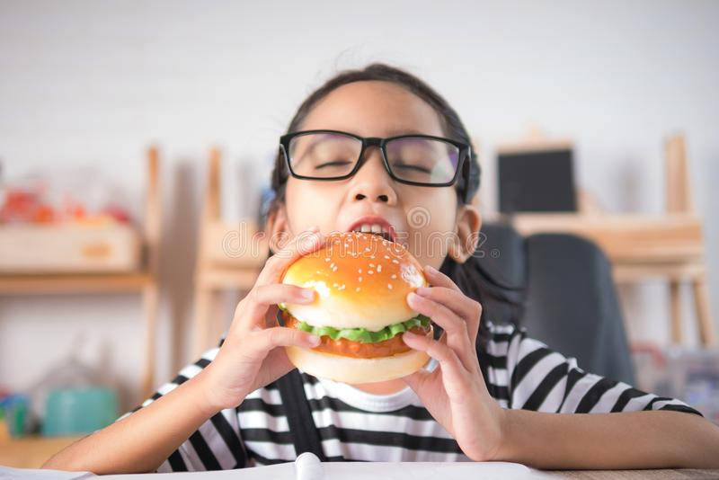 Asian little girl eating hamburger on wooden table royalty free stock images